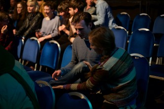 Two audience members sat in seats, one trys to cross the others leg