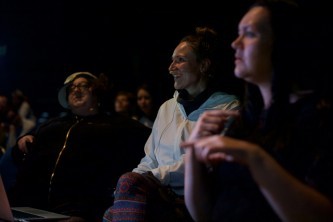 The artists in a gloomy space smile as they listen to the audience