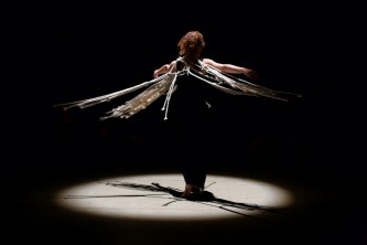 A member of Ueinzz is spotlit as they twirl wearing ropes