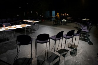 A dark room is set out with tables and chairs in preparation for a workshop