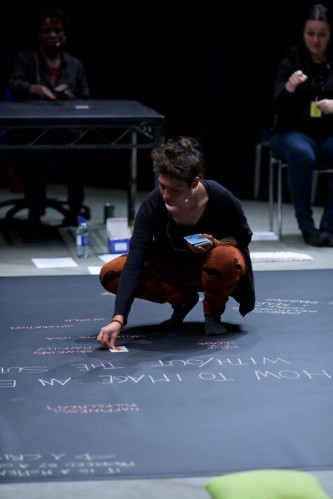 Valentina kneels as she places a tarot card on a chalked word map on the floor