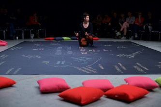 Valentina kneels on a map of words and links written in chalk on black lino