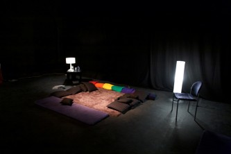 In a dark room, coloured blankets and cushions are arranged