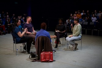 Five people sit in a group in the middle of a space, in discussion