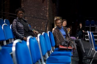 Hortense Spillers in a row of blue chairs smiles at the camera
