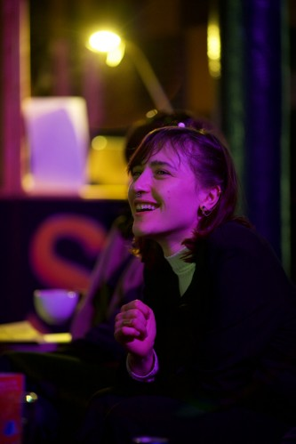 An audience member bathed in pink light laughs