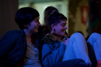 Two audience members in profile laugh