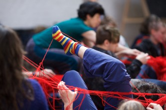 A stripey socked foot sticks up in the air with red wool attached to it