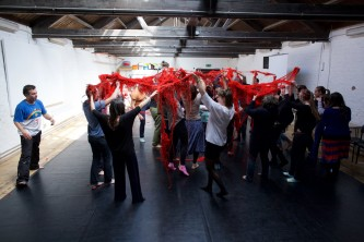 Particpants hold up a big mass of red wool above their heads