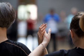 A close up of two Participants touching raised hands lightly