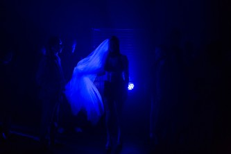 A figure with a long veil moving from a corner in blue light