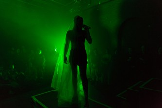 A figure lit from behind by green light holding a microphone