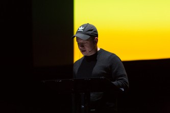 Huw Lemmey reading with a headset mic in front of a yellow screen