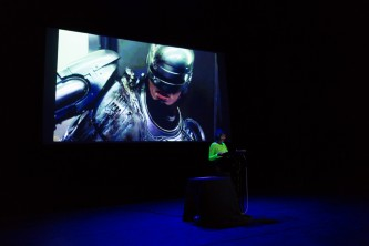 Robocop off to one side on a screen behind Jackie Wang