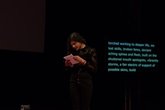 Nat Raha reading from a booklet on stage at EPISODE 9