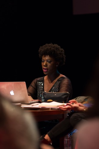 a woman reading from a laptop on a stage