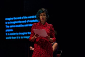 Jackie Wang reading in a red dress on stage in front of a transcription screen