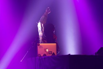 Moor Mother holding her hand up behind a laptop in purple light