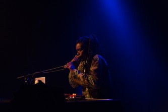 Moor Mother holding a microphone standing behind a mixer