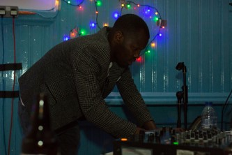 DJ Alieu operating some equipment in coloured light at Kinning Park Complex