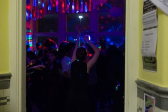 Through a door there is a party with disco lights and dancing