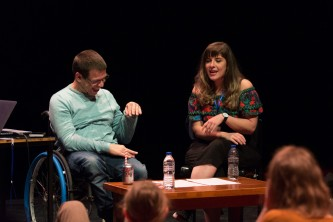 Robert Softley Gale laughing with hand raised next to Maxine Meighan on stage