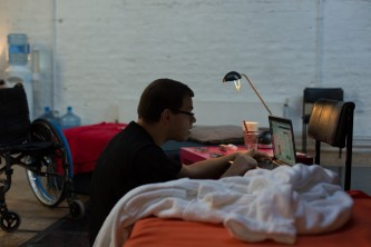 Robert Softley Gale doing something with a laptop next to a dressing gown