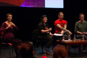 3 people on stage discussing sex work and politics, BSL interpreter stage right