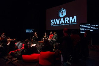 A discussion on stage amidst red cushions and audience members at EPISODE 9
