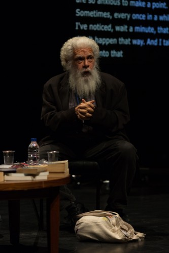 Samuel R Delany beared, seated on stage near a table his tote bag on the floor