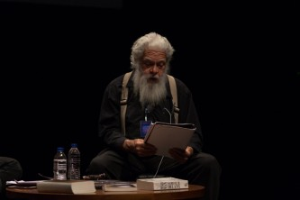 Samuel Delany reading from a document on stage; bearded with grey hair & braces