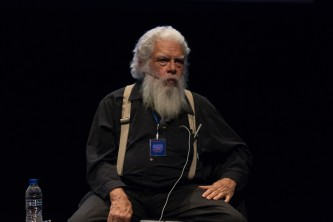 Samuel Delany wearing black and bearded with one hand in his lap