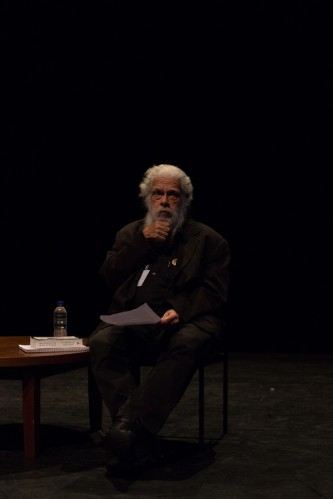 Samuel Delany holding his fist to his chin seated next to a table with papers