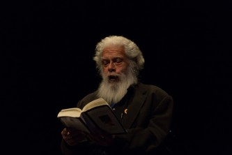 Samuel Delany wearing black and bearded reading from a book