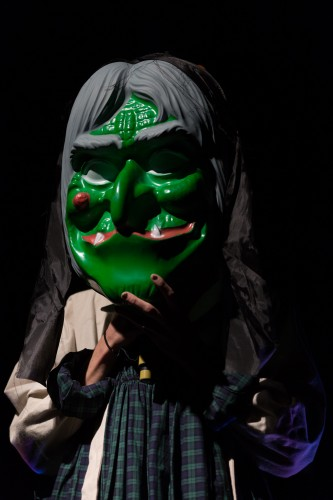 A huge green witch mask obscures a performer's features