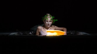 Sgàire sitting in a pool of water holding a yellow basin