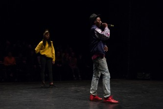 Mele Broomes and Storyboard P standing on a stage he is using a microphone