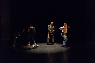 Four people dancing on stage during performance by Storyboard P
