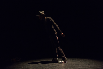 Storyboard P leaning in brown clothes during a dance performance at EPISODE 9