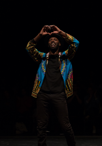 Storyboard P making a heart shape with his hands during a dance performance