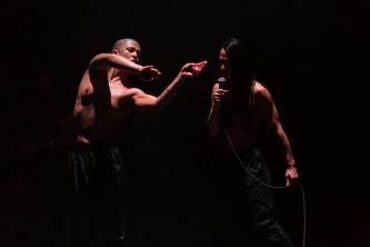 Two people stand side by side in a dark room. Hands point towards other person
