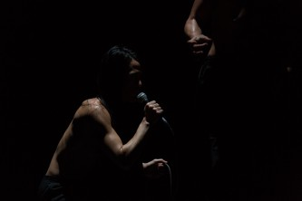 Crouched figure with microphone. They are in a dark room and their torso is lit