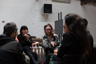 A group of people have a discussion in a workshop