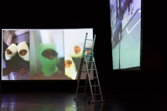 Two large screens on a stage with images of people wearing green balaclava