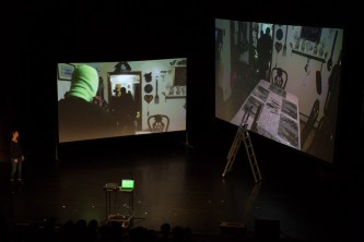 Two large screens on stage. Images of a dining table, someone wears a balaclava
