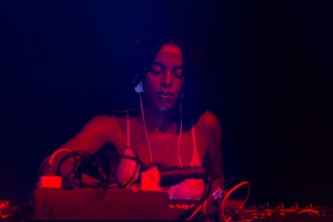 Juliana Huxtable bathed in red light leans over a mixer as they DJ