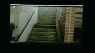 Live video feed projected on screen of a stairwell with concrete and brick