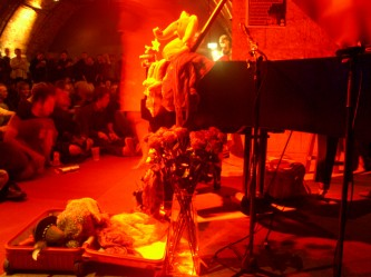Charlemagne's piano covered in soft toys and red light