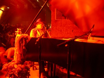 Charlemagne Palestine seated at a piano in red light, small bear to his right