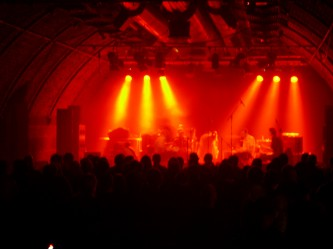 Current 93 on stage in the distance under red lights